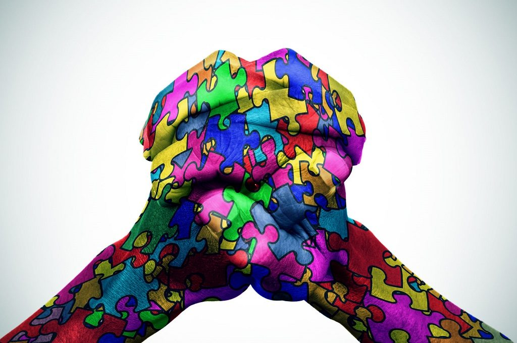 54039116 - man hands put together patterned with many puzzle pieces of different colors, symbol of the autism awareness, with a slight vignette added